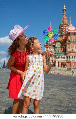 Mother and daughter are blowing on colorful pinwheel on Red Square in Moscow