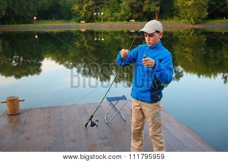 Young boy adjusts float rods on dock at river early morning.