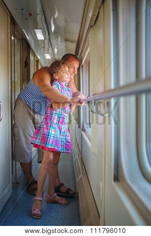 Grandfather with granddaughter stand in corridor coupe and look through window