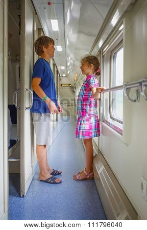 Brother and sister standing in corridor train compartment and laughing