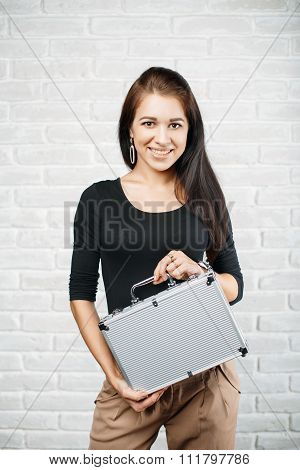 Young Girl Holding Aluminum Case Against A White Brick Wall.