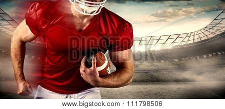 American football player holding ball against rugby stadium