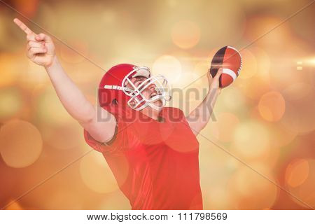 A triumph of an american football player against orange abstract light spot design