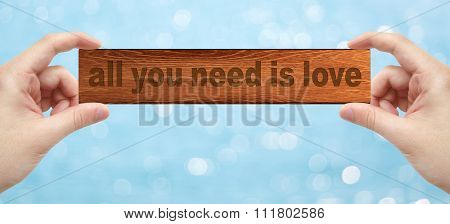 Hands Holding A Wood Engrave With Word All You Need Is Love