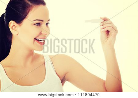 Happy woman holding pregnancy test.