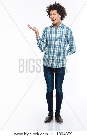 Full length portrait of a cheerful afro american man holding copyspace on the palm isolated on a white background