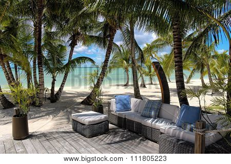 Rattan chairs on a wooden deck near the beach