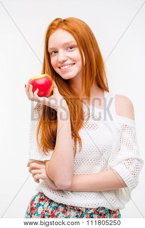 Beautiful cheeful happy attractive natural girl with long red hair holding an apple