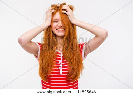 Funny amusing cheerful girl with messy tousled long red hair holding her hands to her head and laughing