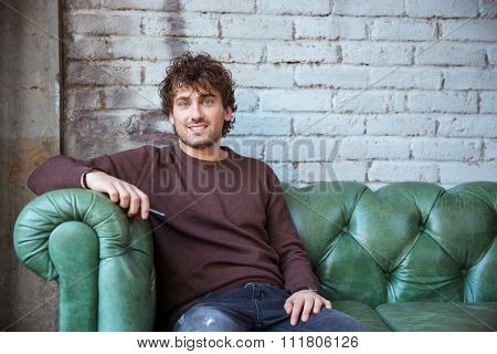 Attractive smiling joyful pleased content positive curly confident male in brown sweetshirt and jeans sitting on green leather couch