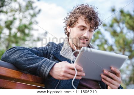 Young handsome content curly man in black jacket sitting on wooden bench, using tablet and listening to music using earphones