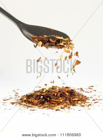 Dried Chili Pepper Falling From Tablespoon