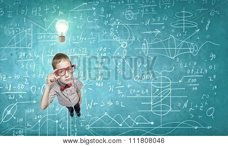 Top view of cute schoolboy in red glasses on chalkboard background