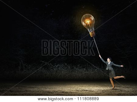 Businesswoman in bowler hat pulling rope with glass light bulb