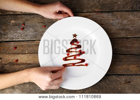Woman making Christmas fir tree made from chocolate on old wooden table