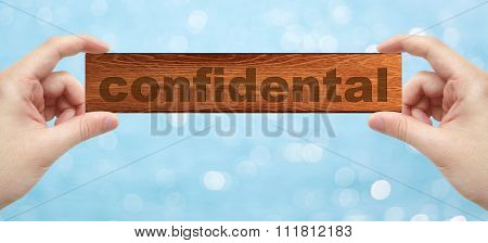 Hands Holding A Wood Engrave With Word Confidental