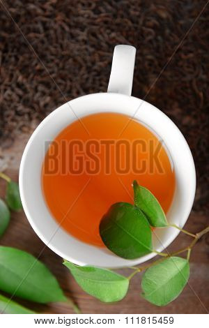 Ceramic cup of tea with scattered tea leaves around on wooden background
