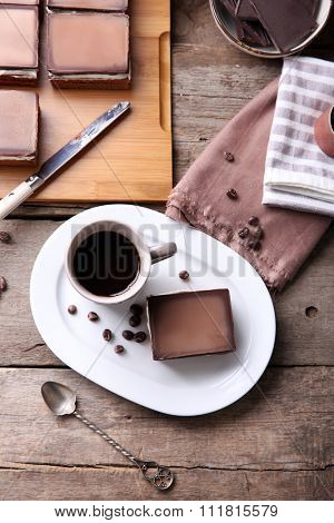 Delicious chocolate brownies on plate and coffee mug, on wooden background