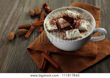 Cup of hot cacao with marshmallow, cinnamon and nuts on brown cotton serviette, close up
