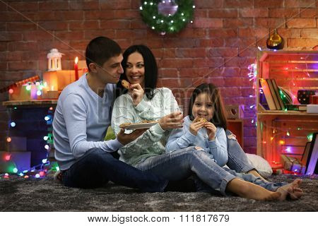 Happy family with milk and cookies in the decorated Christmas room