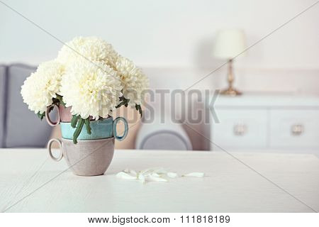 Beautiful flowers in vase on table in room on bright background