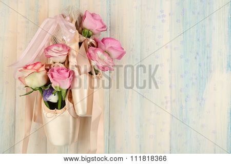 Decorated ballet shoes with roses in it hanging on light wooden background