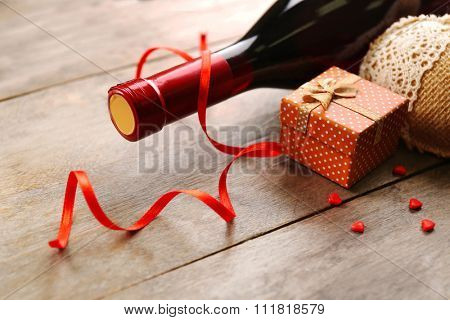Setting of a bottle of wine, a gift in the box and other decoration, on wooden background
