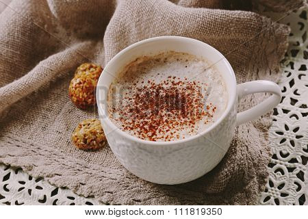 Cup of hot cacao with sweets on cotton serviette