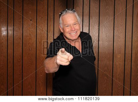 A good looking man Points directly at You via pointing straight into the camera lens, against a wood panel wall with room for your text. Focus on the mans finger with his face slightly out of focus.