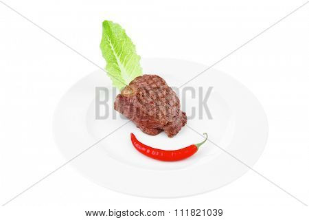 bbq : beef (pork) steak garnished with green lettuce and red chili hot pepper on white plate isolated over white background