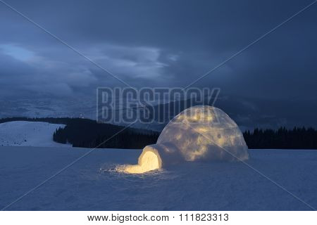 Snow igloo. Winter in the mountains. Evening Landscape with shelter for extreme tourists. Adventure Outdoors