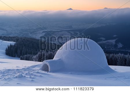 Snow igloo on a mountain hill. Winter landscape. Adventures in the winter campaign