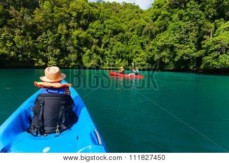 Family with kids paddling on colorful kayaks at mangroves during summer vacation