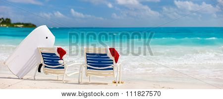 Panorama of two sunloungers with Santa hats on beautiful tropical beach with white sand and turquoise water, perfect Christmas vacation banner