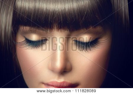 Beauty Model Girl Face with perfect long eyelashes and Fringe hairstyle. Brunette young woman facial makeup closeup. Perfect eye make up for brunette