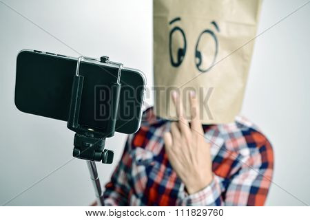 a young caucasian man with a paper bag with a funny face takes a self-portrait with a selfie stick while gives a V sign