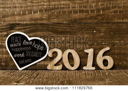 wooden numbers forming the number 2016 and a heart-shaped chalkboard with some wishes for the new year, such as peace, love and happiness, on a rustic wooden surface