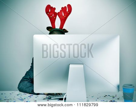 a young caucasian businessman with a reindeer antlers headband, behind the screen of his computer, sitting at his office desk covered with confetti