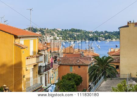 View of colorful rooftops and Mediterranean sea harbor with boats in old medieval town Villefranche-sur-Mer on French Riviera, France.