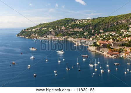 Coastal aerial view of Cap de Nice and medieval town Villefranche-sur-Mer on scenic French Riviera with leisure boats anchored in Mediterranean sea harbor
