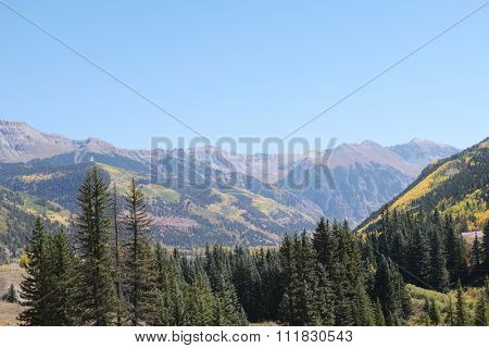 Scenic mountain landscape in Colorado with forested valleys and high peaks under a sunny clear blue sky
