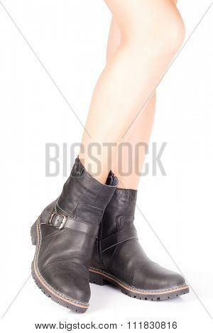 Beautiful female legs in men's leather boots with buckles