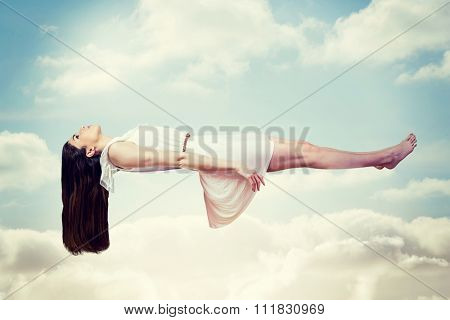 Girl in white dress floating in air against blue sky with white clouds