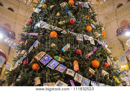 Moscow, Russia - December 11, 2015: Christmas tree decorated with Christmas balls, candy and garland of old postcards at State Department Store