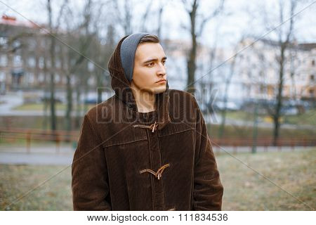 Young Stylish Guy In An Old Jacket And Knit Cap On A Background Of The Autumn Park