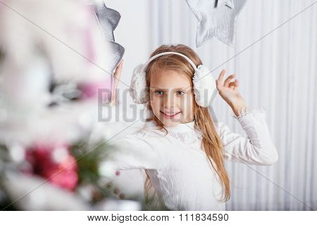Beautiful Little Girl In Earmuffs Decorating Christmas Tree With Toys And Balls.