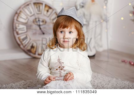 Portrait Of A Beautiful Little Girl In A White Dress And A Crown In The Interior With Christmas Deco