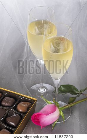 Two Glasses of Champagne, Single Pink Rose and an Open Box of Gourmet Chocolates