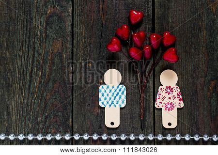 Two Painted Wooden Little Man And A Branch With Hearts