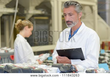 Man holding clipboard looking at plastic packages
